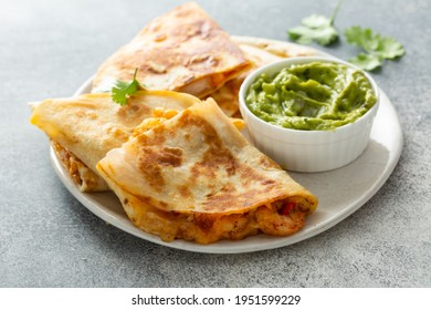 Shrimp and cheese quesadillas with red pepper and cilantro served with guacamole