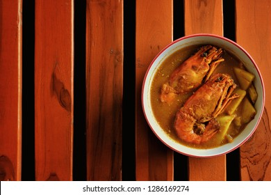 Shrimp curry,or Sour soup made of Tamarind Paste with Shrimp Southern Thai food is very spicy on wooden background.