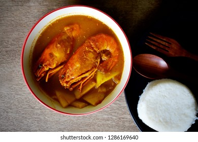 Shrimp curry,or Sour soup made of Tamarind Paste with Shrimp Southern Thai food is very spicy with rice on wooden background.