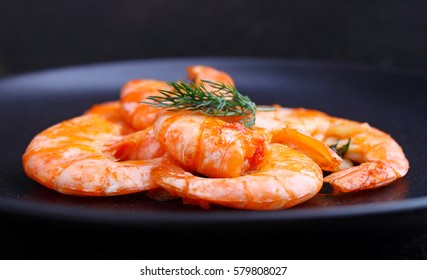 shrimp and dill in black plate on a black background