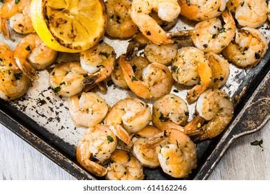 Shrimp dinner on metal pan with grilled lemon wedge
