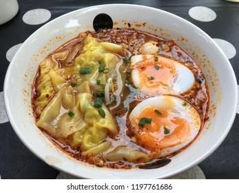 Shrimp dumplings with boiled egg in Tomyum soup.