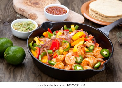 Shrimp fajitas with bell pepper, onion, and jalapeno in cast iron skillet ready to be served. Guacamole, salse, and tortillas.