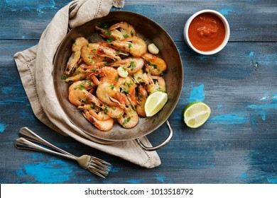 Shrimp fried in frying pan with garlic and spices. Blue wooden nautical background