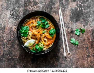 Shrimp laksa soup on a dark wooden background, top view. Copy space. Asian style food