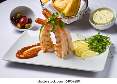Shrimp, lemon. cocktail sauce, olives, and bread on a white plate
