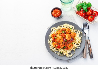 Shrimp linguine Puttanesca pasta with shrimps in spicy tomato basil sauce,  on a gray plate, top view, horizontal, copy space