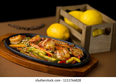Shrimp main course with zucchini, carrots, red pepper and sesame in cast iron plate on a wooden base with yellow lemon in a wooden crate