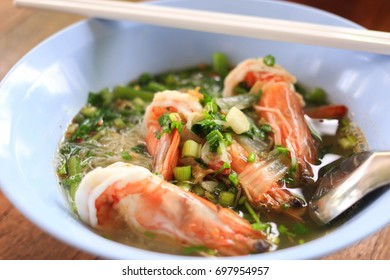 Shrimp noodles Put in a blue bowl, delicious, sour, sweet, spicy with chopsticks and spoon.