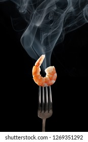 shrimp on the fork with black background. king shrimp with smoke on fork close up. tiger shrimp on silver fork