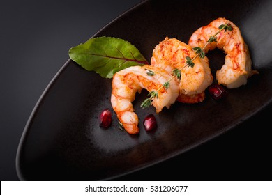 Shrimp on the grill under a pomegranate sauce. Exquisite dish of seafood.