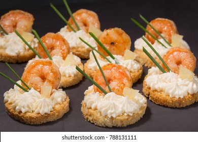 canapé with shrimp on white bread, decorated with a slice of lemon, on a black slide, a beautiful presentation