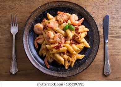 Shrimp pasta with sun dried tomatoes and basil in creamy mozzarella sauce. View from above, top studio shot