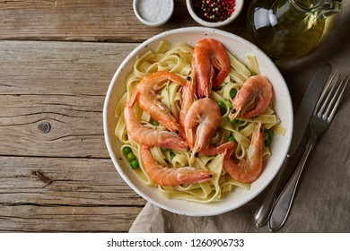 Shrimp, pasta tagliatelle, green peas, dill. White plate on old rustic wooden table, top view, copy space