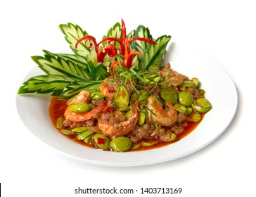 Shrimp paste stir fried curry with Bitter bean or stink bean and fresh shrimp. Thai food fusion style decorate with carved leaf cucumber and chili pepper side view isolated on white background