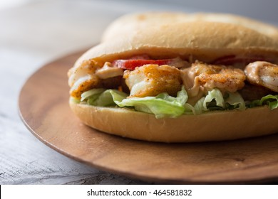 Shrimp po boy sandwich with tomato, lettuce and remoulade sauce on a wooden plate.