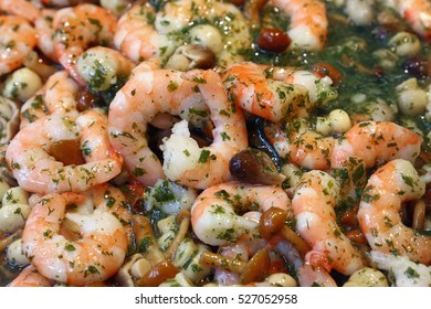 Shrimp prawns seafood salad with mushrooms and green herbs in dressing close up, high angle view