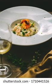 risotto aux crevettes avec pois et herbes sur plaque blanche