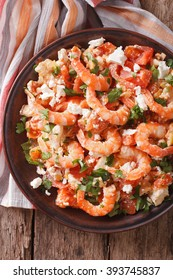 Shrimp saganaki with tomato and feta cheese on a plate on a table close-up. vertical view from above