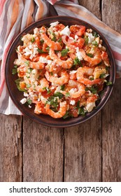 Shrimp saganaki with tomato and feta cheese on a plate on a table. vertical view from above