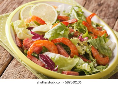 shrimp salad with chorizo and mix lettuce close-up on a plate on the table. horizontal