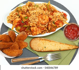 Shrimp Sausage Chicken Jambalaya with Potatoe Wedges and Garlic Bread on slate serving tray over white.