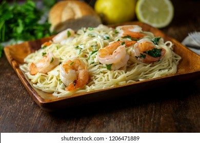Shrimp scampi with angel hair pasta surrounded by cooking ingredients