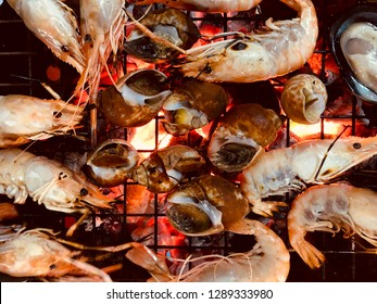 Shrimp and Spotted babylon are grilled on a charcoal stove. Seafood mix grilled on stove.