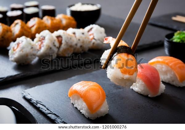 黒い皿に割り箸でエビの寿司握り。箸と裏巻き、細巻きを背景に握りの接写。レストランで黒板料理に日本食を食べる。