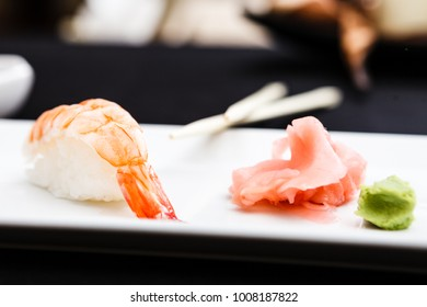 Shrimp sushi served on a plate with ginger and wasabi