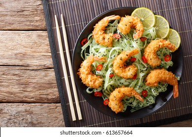 Shrimp tempura with green pasta and sesame close-up on a plate. horizontal view from above
