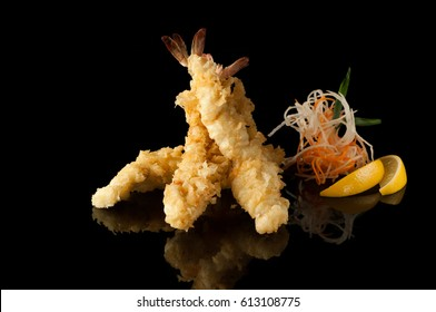 shrimp in tempura with lemon slices and salad on a black background with reflection