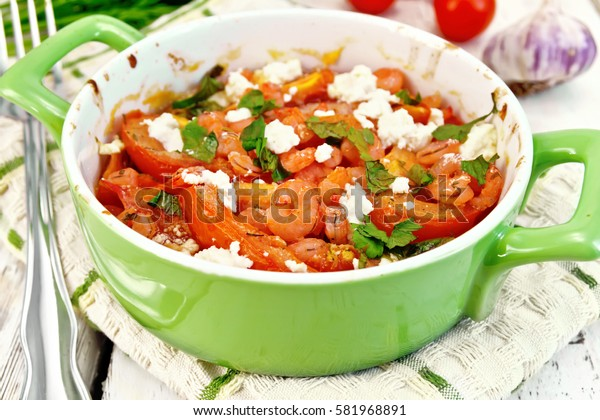 Shrimp and tomatoes baked with salty feta cheese in a roasting pan on a kitchen towel, garlic on a wooden boards background