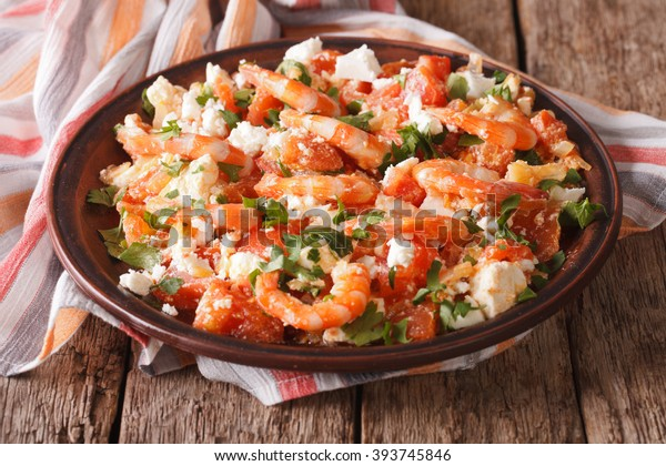 Shrimp with tomatoes and feta cheese on a plate on a table close-up. horizontal