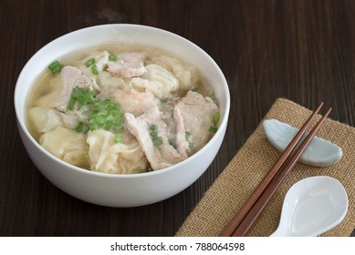 Shrimp wonton with braised pork in hot soup in white bowl on wooden table Asia food  / Select focus image