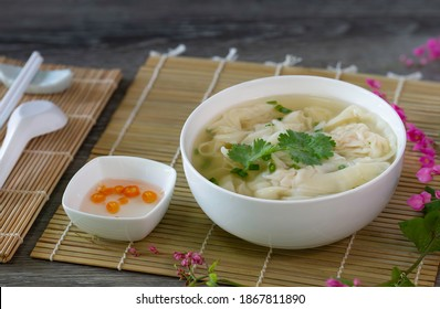 Shrimp wonton in soup on bamboo mat and wooden table,   Select focus image Space for text