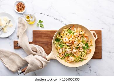 Gambas y fideos de calabacín o zoodles con copos de parmesano y chile cocidos en una sartén de hierro fundido
