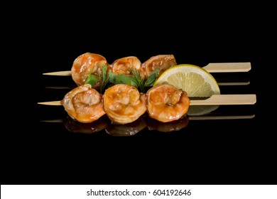 Shrimps cooking on a grill. On a black background with reflection