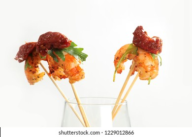 shrimps with the dried tomato and arugula on sticks, a canape stand in a glass on a white background