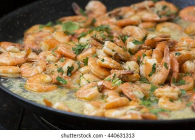 Shrimps fried on pan with fresh herbs in a closeup