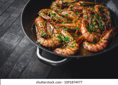 Shrimps fried in a pan. Classic recipe - parsley, garlic, chilli