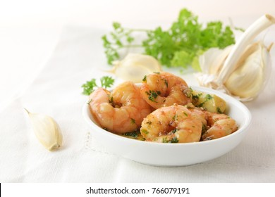 shrimps with garlic, olive oil and parsley in sherry sauce in a white bowl, spanish tapas appetizer gambas al ajillo, white napkin background, copy space, selected focus, narrow depth of field