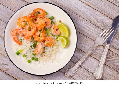 Shrimps with ginger rice and green peas, lime on white plate on wooden background