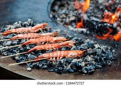 Shrimps grilled on wooden skewers laying near grill