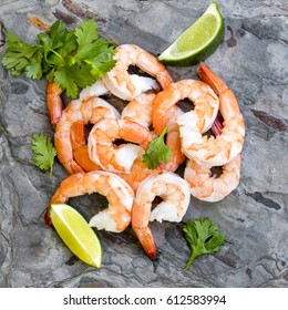 Shrimps on slate, top view, with lime and cilantro or coriander.