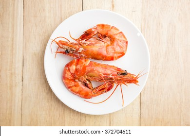 Shrimps on white dish over wood table
