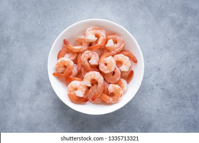 Shrimps, Prawns in bowl, top view, copy space. Fresh seafood ingredient - shrimp tails ready for cooking. Boiled prawns.