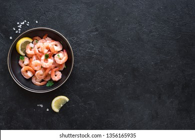 Shrimps, Prawns in bowl, top view, copy space. Fresh seafood background - shrimp tails on black. Boiled Prawns.