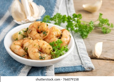 shrimps or prawns and garlic in olive oil with parsley garnish in a white bowl, blue napkin on a rustic wooden table, spanish tapas appetizer gambas al ajillo, selected focus, narrow depth of field