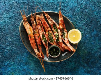 Shrimps Prawns skewers with garlic and fresh herbs on a blue background, top view. Barbecue srimps prawns Seafood